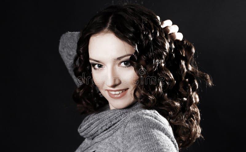 La bella giovane donna in maglione ed in stivali posa per la macchina fotografica fotografia stock libera da diritti