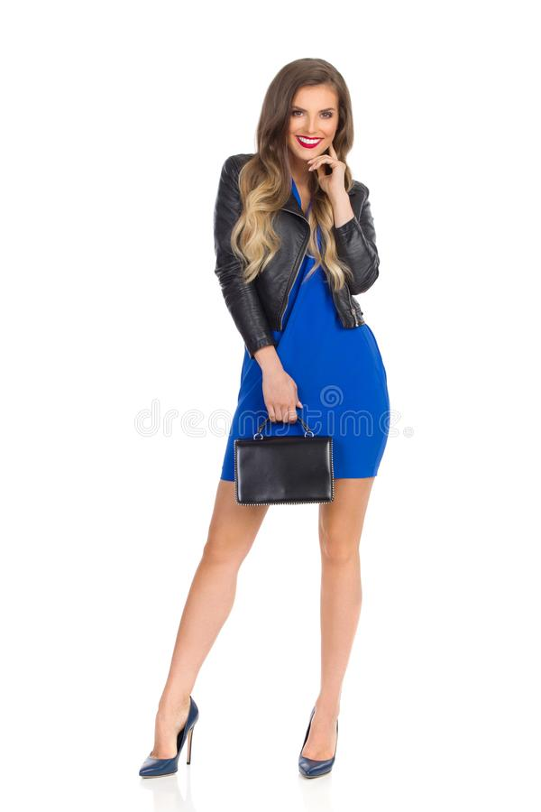 La bella giovane donna in Mini Dress And Leather Jacket blu sta tenendo la borsa nera fotografie stock libere da diritti