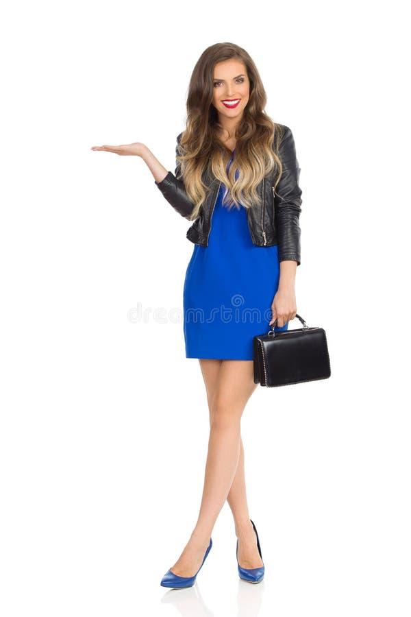 La bella giovane donna in Mini Dress And Leather Jacket blu sta tenendo la borsa nera, sta presentando ed esaminando la macchina  fotografie stock