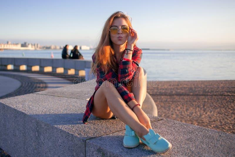 La bella giovane donna nella sera sulla spiaggia, si siede immagini stock libere da diritti