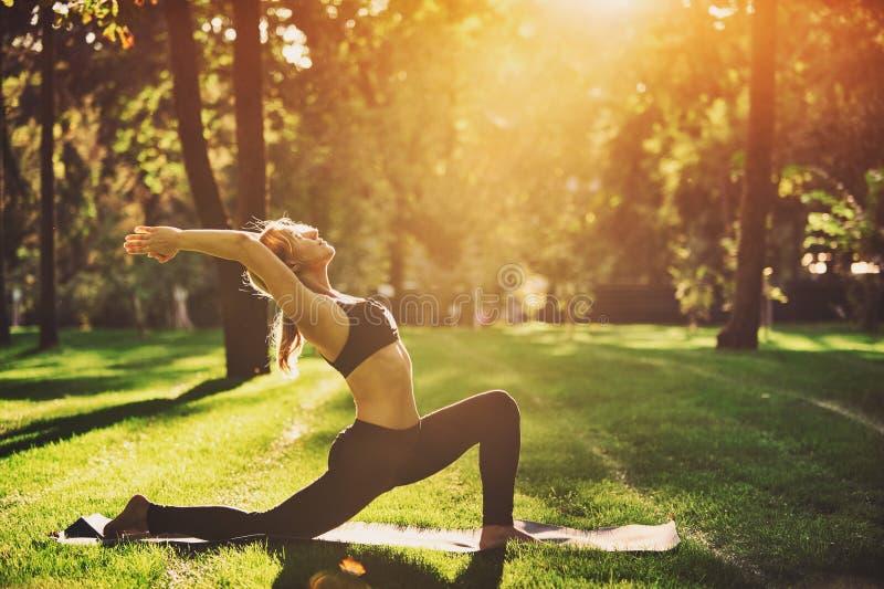 La bella giovane donna pratica il asana Virabhadrasana 1 di yoga - posa 1 del guerriero nel parco al tramonto fotografia stock libera da diritti