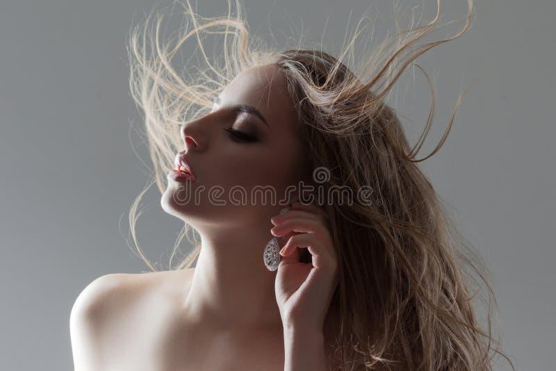 La bella giovane donna regola il suo orecchino, primo piano del ritratto Capelli di volo fotografia stock libera da diritti
