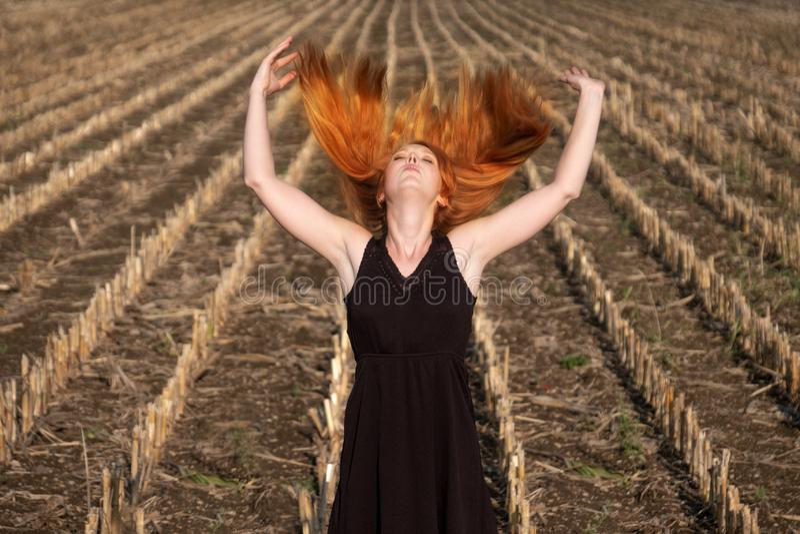 La bella giovane donna sexy vitale, in breve vestito nero dall'estate in natura sul campo, alza le sue armi e getta il suo rosso  immagini stock libere da diritti