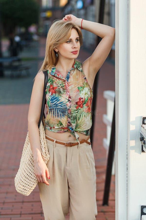 La bella giovane donna si è vestita in camicia tropicale e nel gallig beige immagine stock