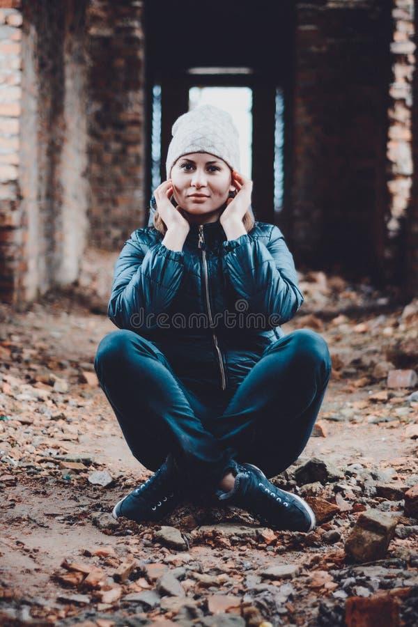 La bella giovane donna si siede in rovine su un fondo arancio in un cappuccio ed in una sciarpa fotografia stock