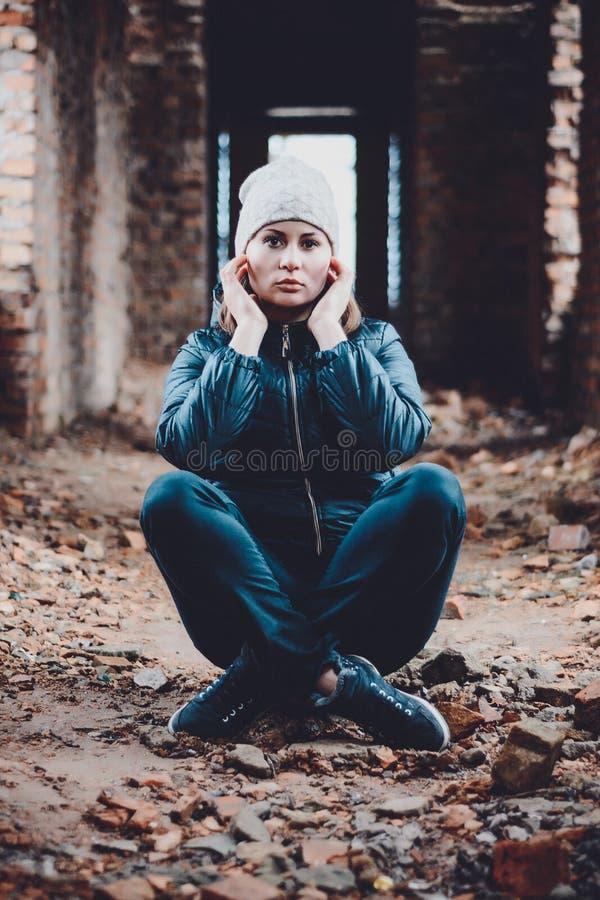 La bella giovane donna si siede in rovine su un fondo arancio in un cappuccio ed in una sciarpa immagini stock libere da diritti