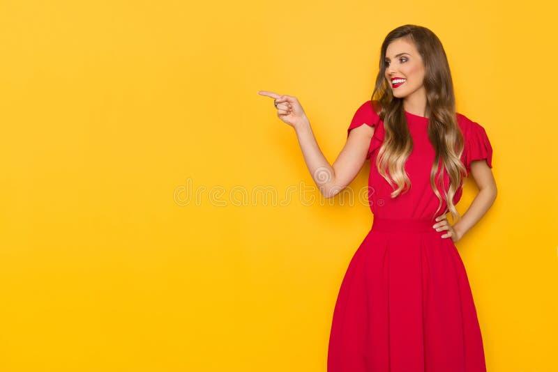 La bella giovane donna sorridente in vestito rosso sta indicando e distogliendo lo sguardo immagini stock libere da diritti