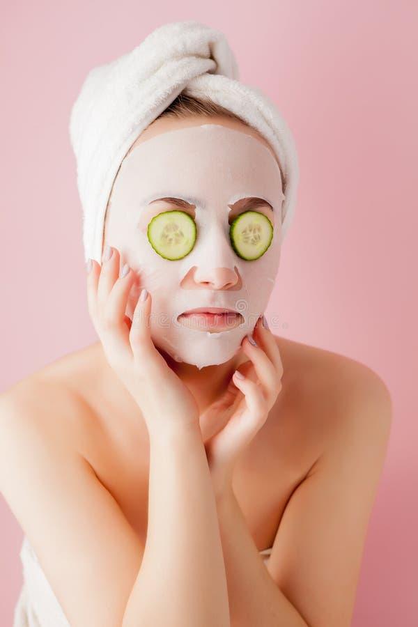 La bella giovane donna sta applicando una maschera cosmetica del tessuto su un fronte con il cetriolo su un fondo rosa fotografia stock libera da diritti