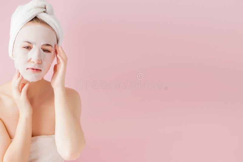La bella giovane donna sta applicando una maschera cosmetica del tessuto su un fronte su un fondo rosa Trattamento di bellezza e  fotografia stock libera da diritti