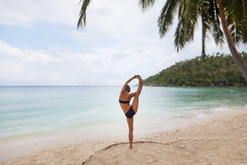 La bella giovane donna sta facendo l'yoga vicino al mare fotografie stock libere da diritti