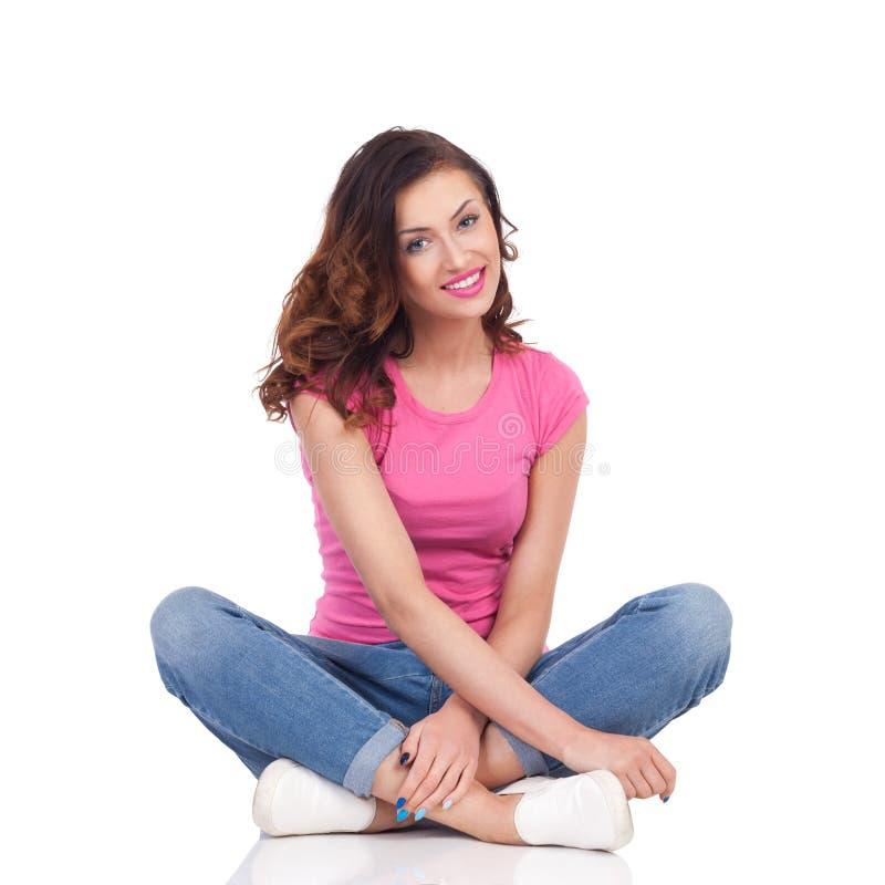 La bella giovane donna sta sedendosi sul pavimento con le gambe attraversate, sta sorridendo ed esaminando la macchina fotografic fotografia stock