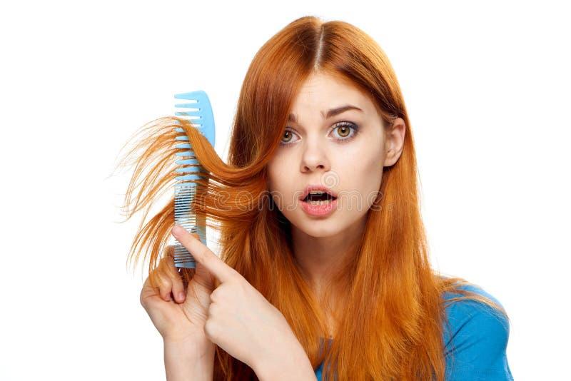 La bella giovane donna su fondo isolato bianco tiene una spazzola per i capelli, taglio dei capelli fotografia stock