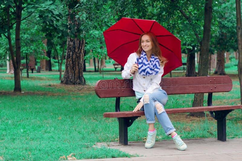 La bella giovane donna sulla natura benches l'ombrello fotografia stock libera da diritti