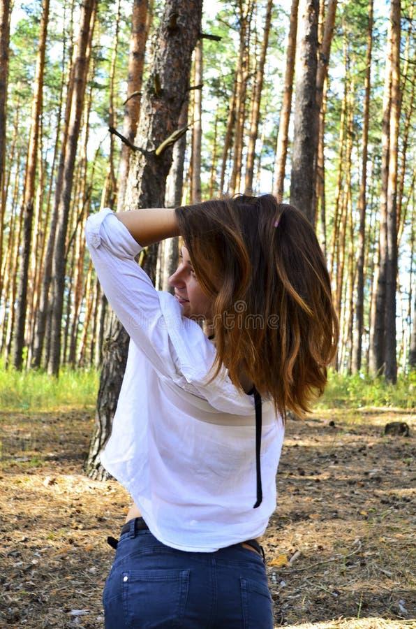 La bella giovane donna tiene i suoi capelli sulle mani immagini stock