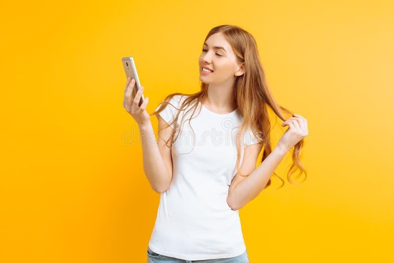 La bella giovane donna, utilizza un telefono cellulare, per messaggio, sguardi allo schermo di uno smartphone, su un fondo giallo immagine stock