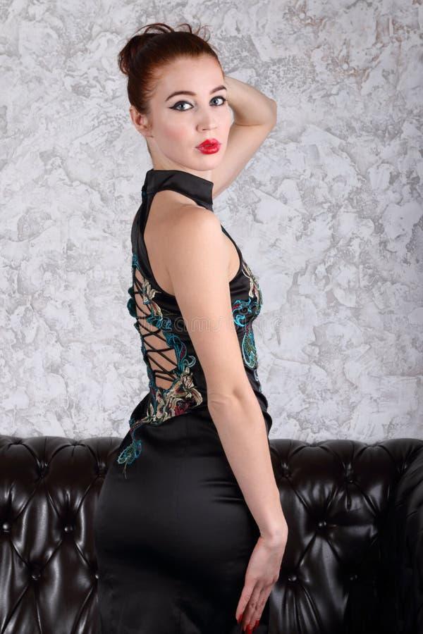 La bella giovane donna in vestito con allacciamento posa vicino al sofà nero fotografia stock libera da diritti