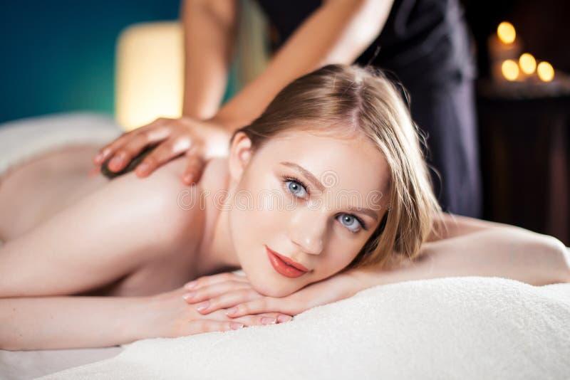 La bella, giovane e donna in buona salute sta avendo massaggio di pietra caldo Stazione termale - 7 immagine stock