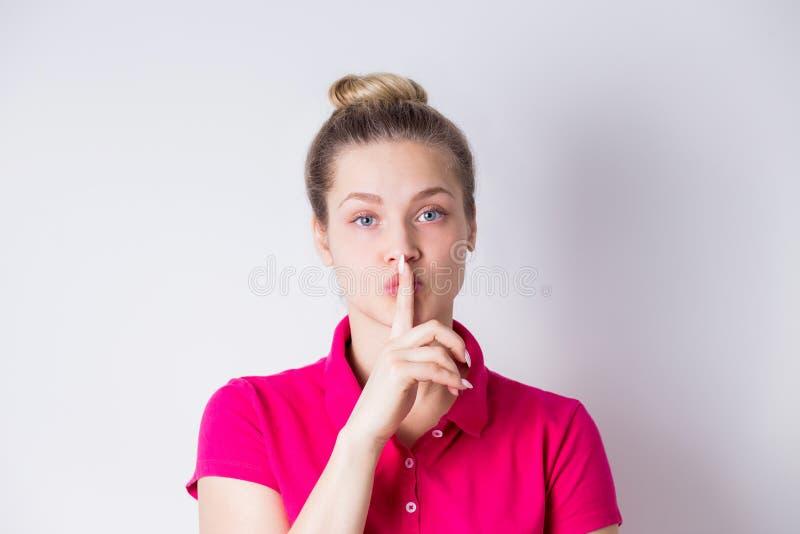 La bella giovane femmina in vestito rosa dimostra il gesto di silenzio, tiene l'indice sulle labbra su fondo bianco fotografie stock