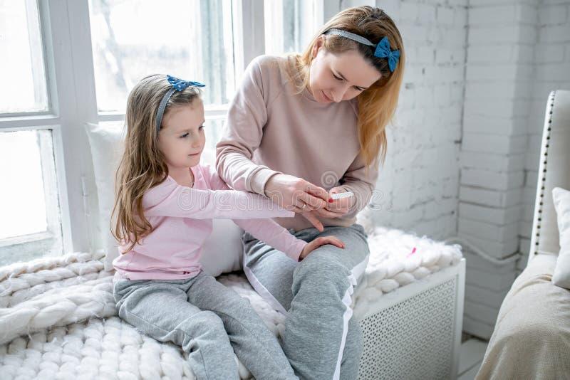La bella giovane madre e la sua piccola figlia stanno sedendo insieme dalla finestra e stanno dipingendo i loro chiodi Cura mater immagini stock libere da diritti