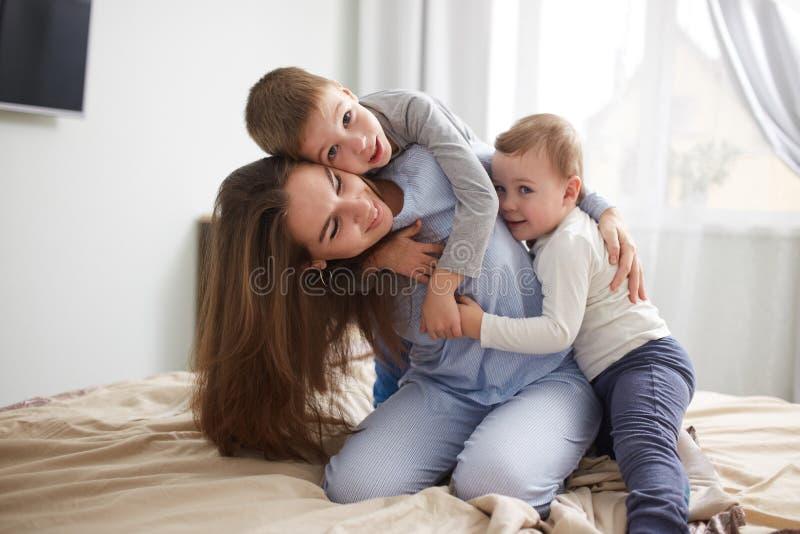 La bella giovane madre e suoi due piccoli i figli vestiti in pigiami si divertono sul letto nella camera da letto accogliente leg immagini stock libere da diritti