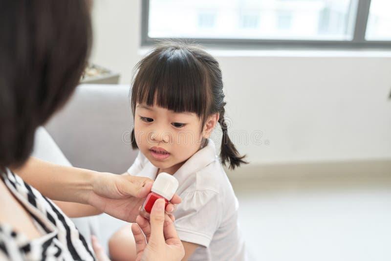 La bella giovane madre sta dipingendo lo smalto per unghie alla sua piccola figlia sveglia fotografia stock