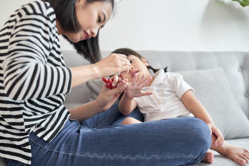 La bella giovane madre sta dipingendo lo smalto per unghie alla sua piccola figlia sveglia fotografia stock libera da diritti