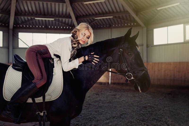 La bella giovane ragazza bionda elegante si trova su una suoi camicia bianca della blusa del cavallo di condimento della concorre fotografie stock