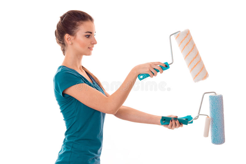 La bella giovane ragazza castana del costruttore in uniforme fa il rinnovamento con i rulli di pittura in sue mani isolate su bia fotografia stock