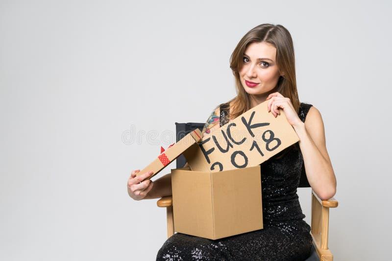 La bella giovane ragazza castana in vestito nero elegante apre un regalo di Natale, sorpreso da un segno ?di scopata 2018 ?su un  fotografia stock libera da diritti