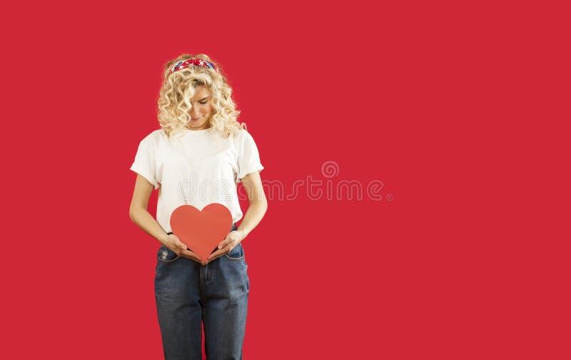 La bella giovane ragazza emozionale con un cuore rosso in sue mani sta stando su un fondo rosso isolato Giorno del `s del bigliet immagine stock