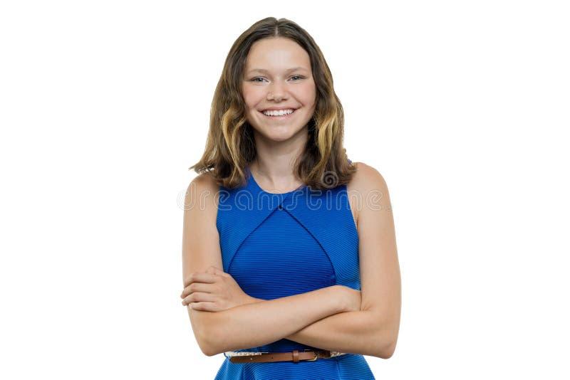 La bella giovane ragazza felice sicura dell'adolescente con le armi ha attraversato sorridere sul fondo bianco, isolato immagine stock