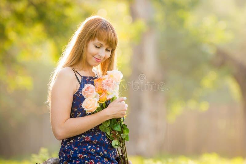 La bella giovane ragazza sexy esamina il mazzo delle rose date alla sua condizione contro un fondo di soleggiato verde vago immagini stock libere da diritti