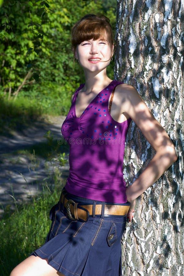 La bella giovane signora in blusa porpora ed il denim fiancheggiano la posa all'aperto immagini stock libere da diritti