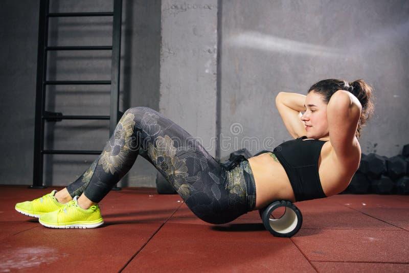 La bella giovane sportiva caucasica della donna utilizza un massaggiatore del rullo della schiuma per rilassamento, allungando i  fotografia stock libera da diritti