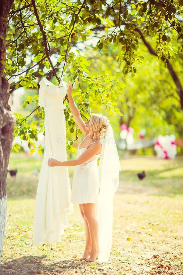 La bella giovane sposa bionda esamina le sue nozze, appendendo su un albero e su un giardino, la mattina della sposa, fuoco selet fotografie stock