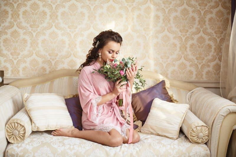 La bella giovane sposa con i capelli scuri si siede su un sofà in una camera da letto Mattina del ` s della sposa fotografia stock libera da diritti