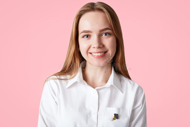 La bella giovane studentessa ha pelle sana, occhi azzurri ed il sorriso positivo, porta la camicia elegante bianca, posa contro b immagine stock