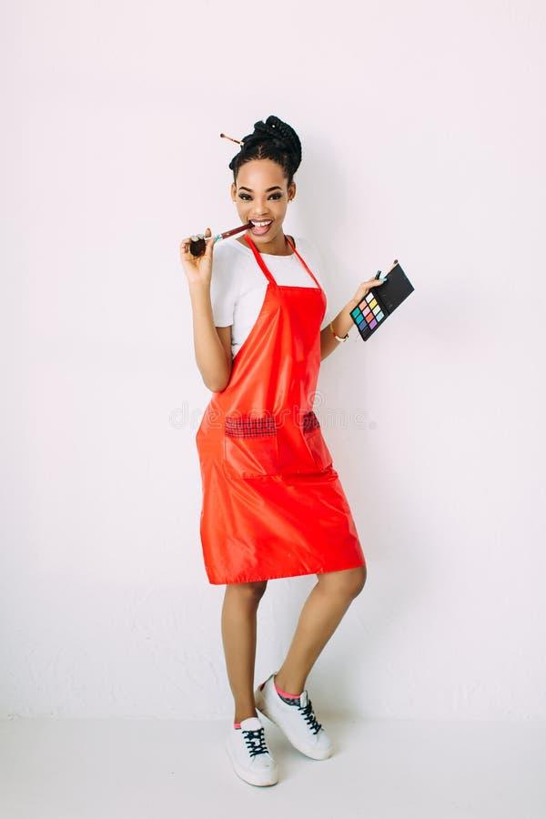 La bella giovane tenuta afroamericana della donna dell'estetista messa di compone le spazzole e gli ombretti, isolati su bianco fotografia stock libera da diritti