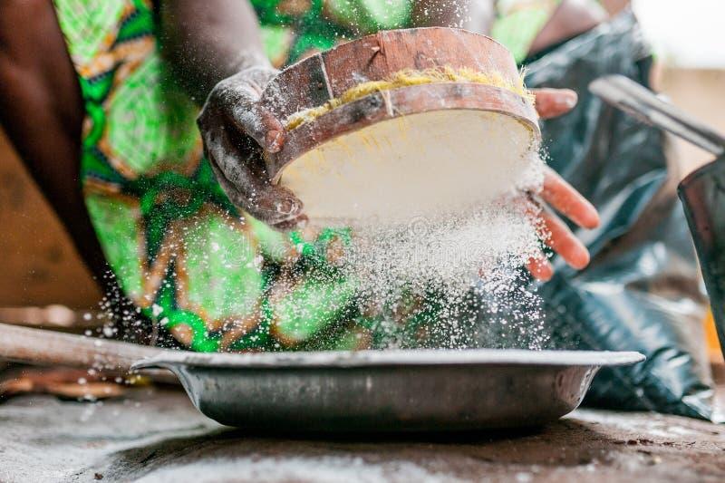 La bella immagine della donna di colore passa la ricerca e vagliare del cereale farina bianca mentre cucina il piatto africano tr fotografia stock