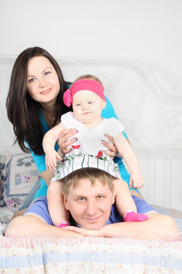 La bella madre ed il bambino sveglio si siedono sul padre sul letto fotografia stock