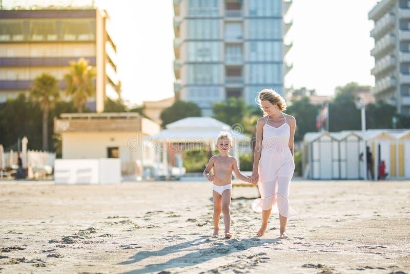 La bella madre felice va di pari passo con il figlio sveglio sorridente alla spiaggia immagine stock libera da diritti