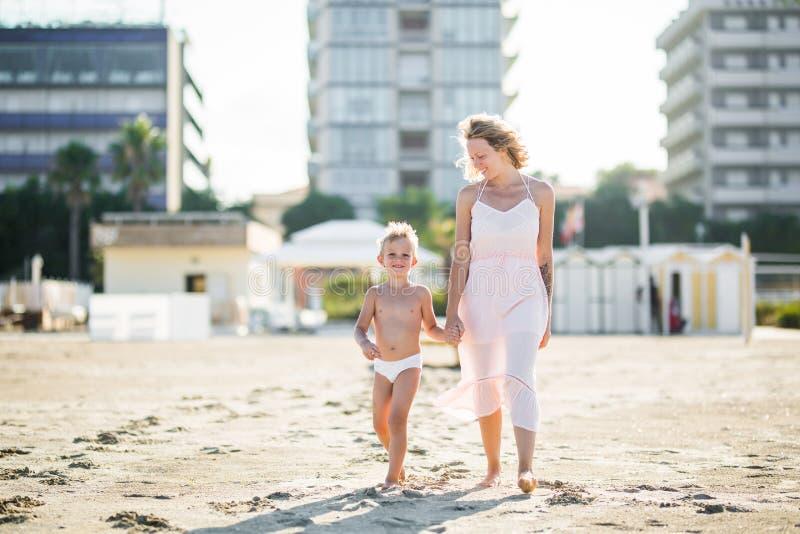 La bella mamma felice va di pari passo con il figlio sveglio sorridente alla spiaggia di sabbia fotografia stock