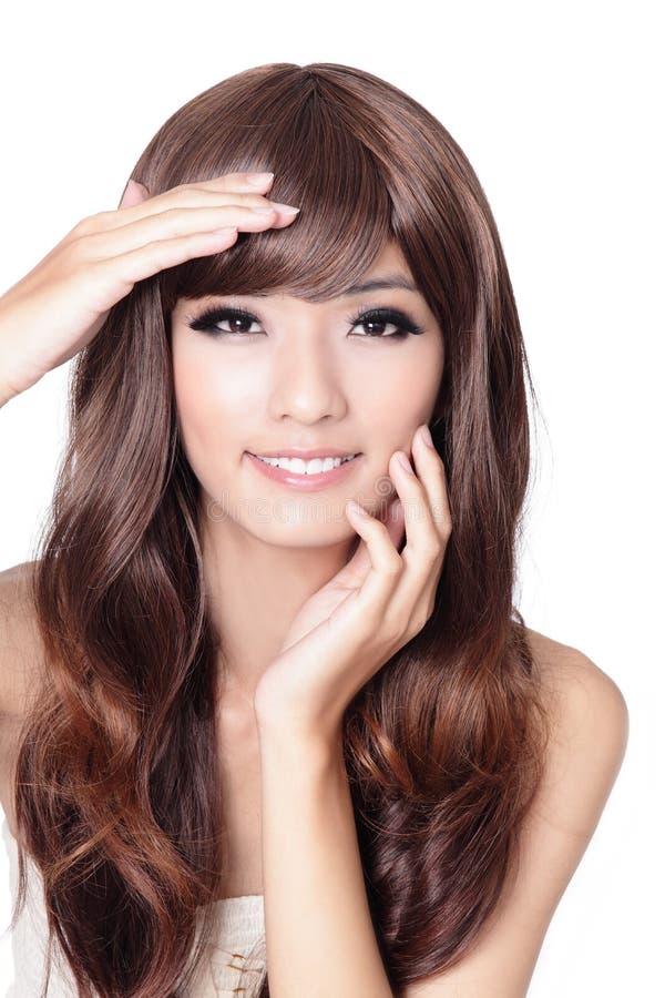 La bella mano asiatica della donna tocca il suo fronte immagini stock