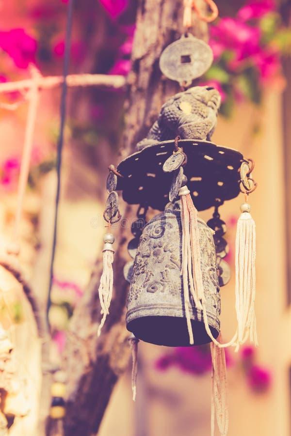 La bella mano ha elaborato la campana cinese del carillon di vento che appende sul ramo di albero in fiori del giardino del tempi fotografia stock libera da diritti