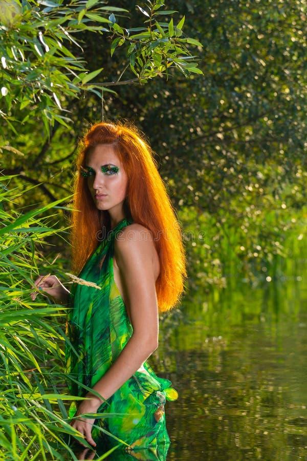 La bella metà della donna rossa vestita dei capelli gode delle acque del fiume fotografie stock libere da diritti