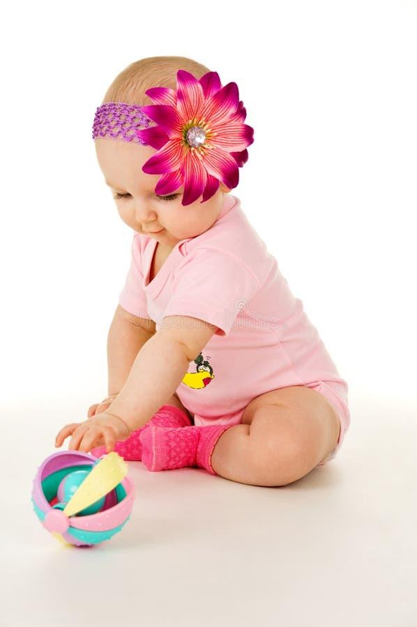 La bella neonata con un fiore gioca immagine stock libera da diritti