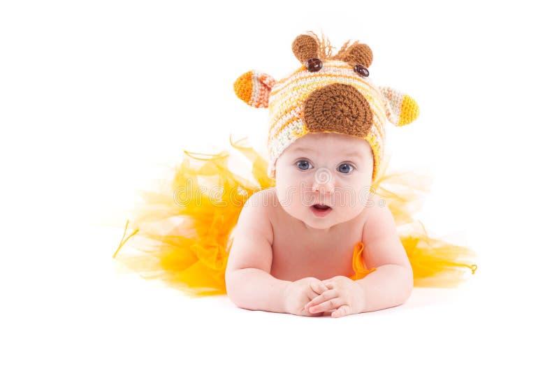 La bella neonata sveglia in costume dei cervi si trova sulla pancia fotografie stock