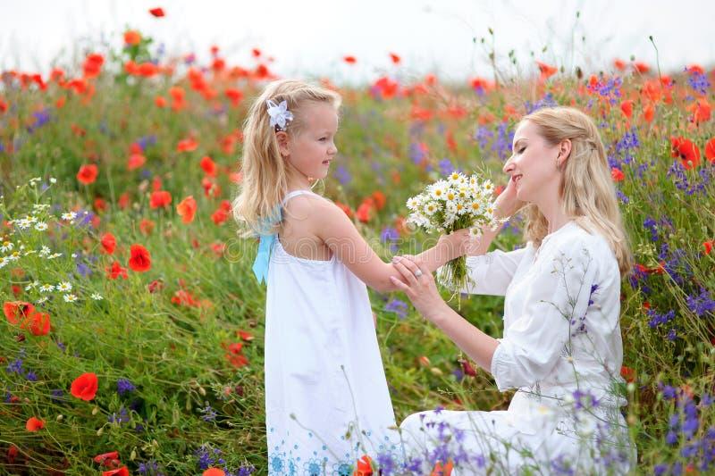 La bella piccola ragazza bionda e sua madre, ha acclamazione felice di divertimento fotografia stock
