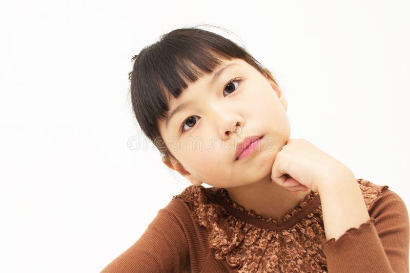 La bella piccola ragazza riposa il suo mento sulle sue mani fotografia stock