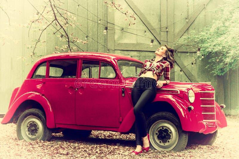La bella pin-up in jeans ed in una camicia di plaid sta appoggiandosi una retro automobile rossa Retro stile fotografie stock libere da diritti